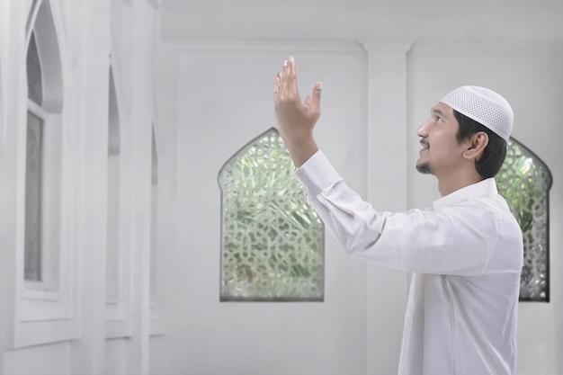 Seitenansicht des asiatischen moslemischen mannes mit trachtenkleid beten