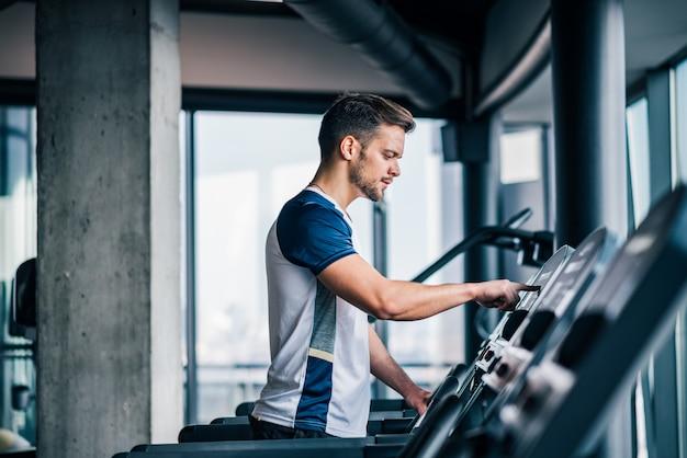 Seitenansicht des athleten geschwindigkeit auf tretmühle justierend, herz training in der turnhalle tuend.