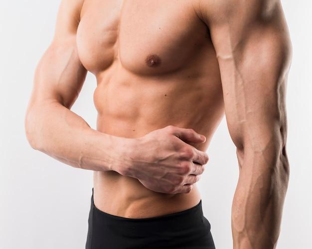 Seitenansicht des athletischen mannes muskeln vorführend