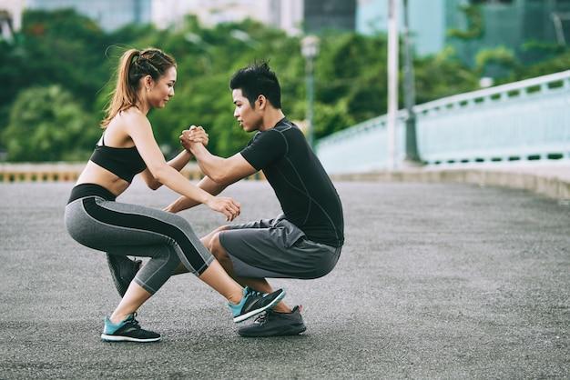 Seitenansicht des athletischen mannes und der frau, die ein bein tun, hocken zusammen draußen