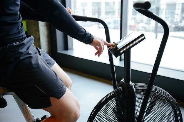 Seitenansicht des athletischen mannes unter verwendung des sich drehenden fahrrads
