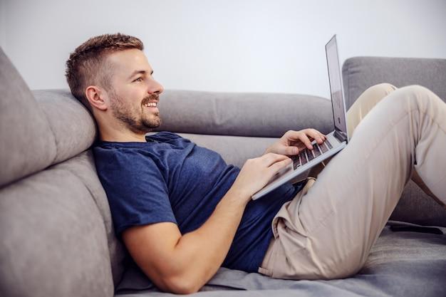 Seitenansicht des attraktiven bärtigen lächelnden mannes, der auf sofa liegt und laptop für das surfen im internet verwendet.