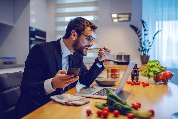 Seitenansicht des attraktiven kaukasischen geschäftsmannes, der smartphone hält, laptop betrachtet und köstliche mahlzeit isst. auf dem esstisch stehen gemüse, laptop und gewürze.