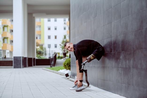 Seitenansicht des attraktiven kaukasischen sportlers mit künstlichem bein, das an die wand lehnt und seinen schnürsenkel bindet.