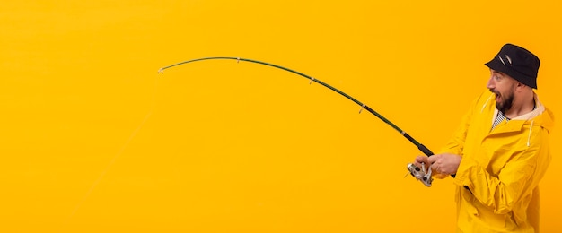 Seitenansicht des aufgeregten fischers angelrute halten