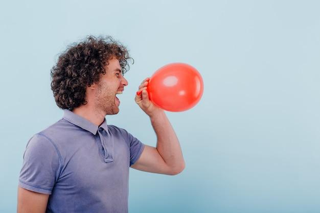 Seitenansicht des aufgeregten lässigen lockigen mannes, der die augen schließt und lacht, während er heliumgas vom ballon einatmet