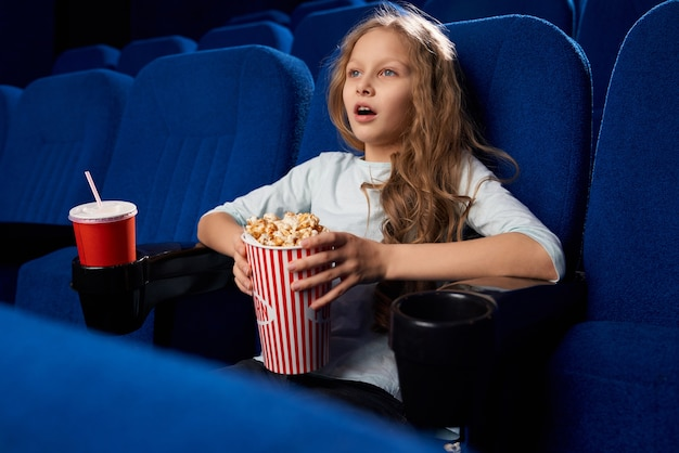 Seitenansicht des aufgeregten weiblichen teenagers, der aktionsfilm im kino sieht. kleines mädchen, das popcorn und süßes wasser hält, ruhe und entspannung während des wochenendes hat