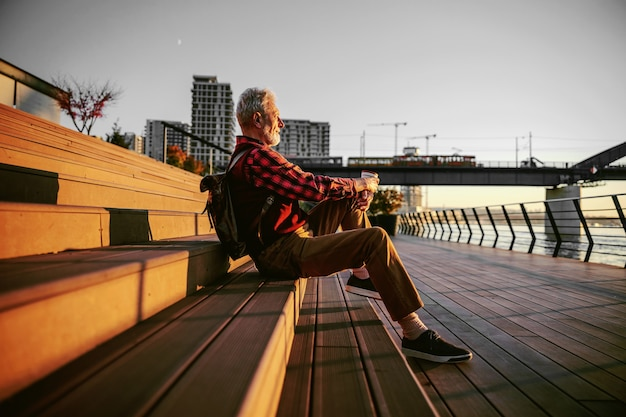 Seitenansicht des bärtigen hipster-älteren mannes, der draußen auf der treppe sitzt und kaffee trinkt.
