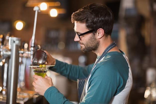 Seitenansicht des barkeepers, der getränke macht, während er brillen trägt