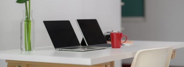 Seitenansicht des bequemen schreibtischs mit laptop, digitalem tablet, becher, kamera, büromaterial und dekoration