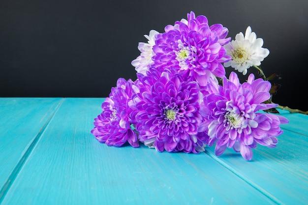 Seitenansicht des blumenstraußes der violetten und weißen farbe chrysanthemenblumen lokalisiert auf blauem hölzernem hintergrund