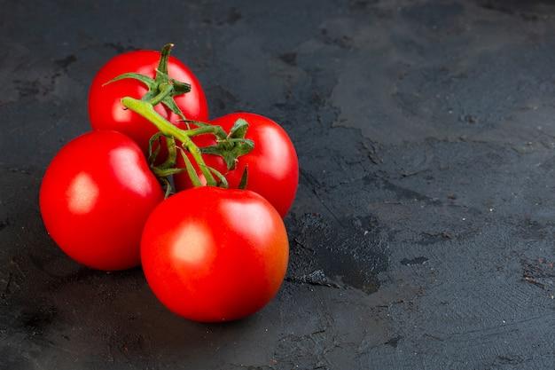 Seitenansicht des bündels frischer tomaten auf schwarz