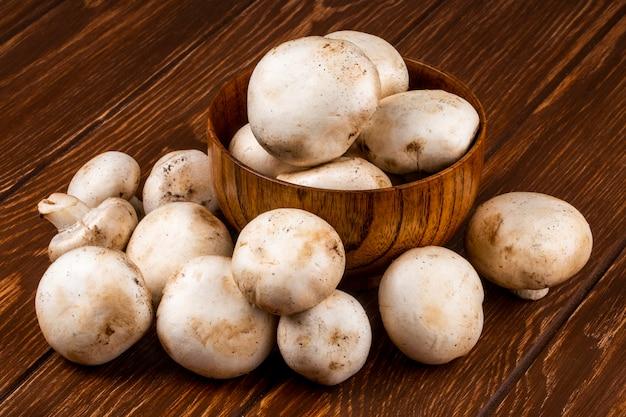 Seitenansicht des champignons der frischen pilze in einer schüssel auf rustikalem hölzernen hintergrund