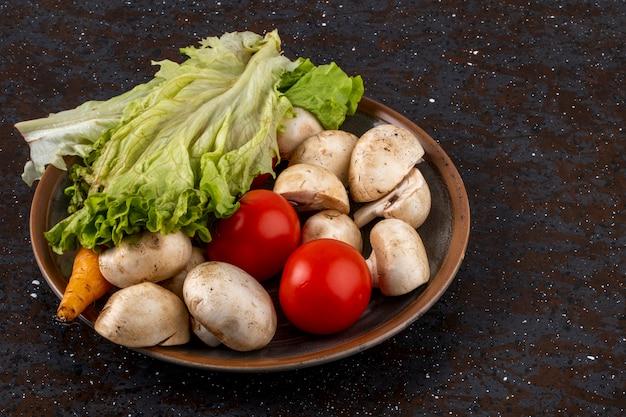 Seitenansicht des champignons der frischen pilze mit reifen tomaten und salat in einer keramikschale
