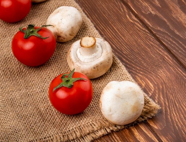 Seitenansicht des champignons der frischen pilze und der frischen tomaten auf sackleinen auf hölzernem hintergrund