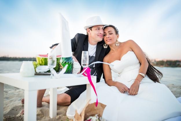 Seitenansicht des charmanten jungen paares, braut und bräutigam stoßen mit champagner an, während sie am tisch mit früchten und blumenstrauß sitzen. hintergrund des flusses und des waldes an einem sonnigen warmen sommertag
