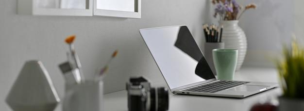 Seitenansicht des designer-schreibtischs mit laptop, malwerkzeugen, kamera und dekorationen