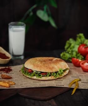 Seitenansicht des döner kebab im fladenbrot auf einem holzbrett mit eingelegten heißen grünen paprikaschoten und ayran-getränk an der holzwand
