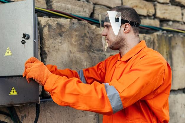 Seitenansicht des elektrikers in uniform mit schutzhandschuhen und gesichtsschutz