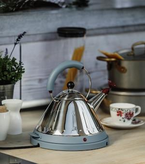 Seitenansicht des elektrischen modernen wasserkochers mit pfeife auf einem holztisch in der küche