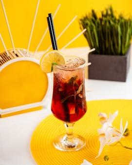 Seitenansicht des erdbeermojitos mit zitronenscheibe im glas auf gelb