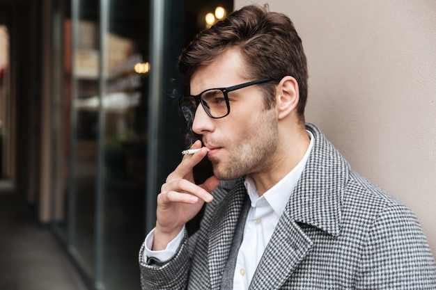 Seitenansicht des ernsten geschäftsmannes in den brillen und im mantel