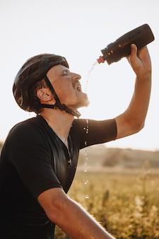 Seitenansicht des erschöpften bärtigen sportlers im schwarzen helm, der wasser von der sportflasche auf seinem gesicht gießt.