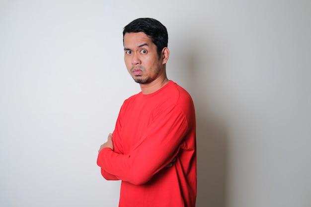 Seitenansicht des erwachsenen asiatischen mannes, der grausamen gesichtsausdruck zeigt