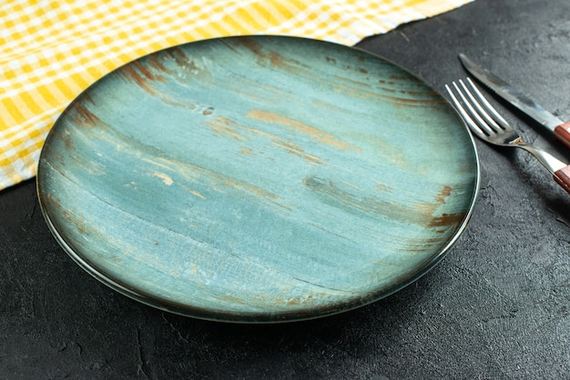 Seitenansicht des essensbestecks im kreuz ein blauer teller und ein gelbes abgestreiftes handtuch auf dunkler oberfläche