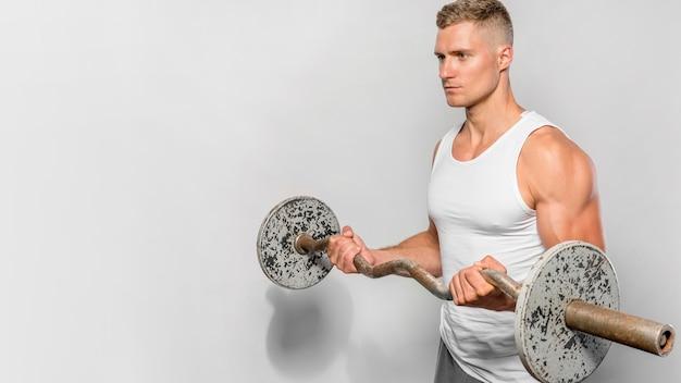 Seitenansicht des fitmanns, der posiert, während er gewichte mit kopienraum hält