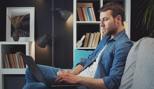 Seitenansicht des fokussierten mannes, der laptop verwendet, der es auf seinem schoß hält, der auf sofa in der flachen, e-arbeit, ablenkung sitzt