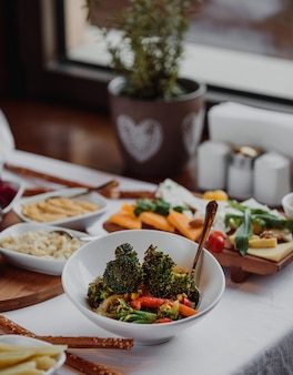Seitenansicht des frischen brokkolisalats in einer weißen schüssel auf dem tisch
