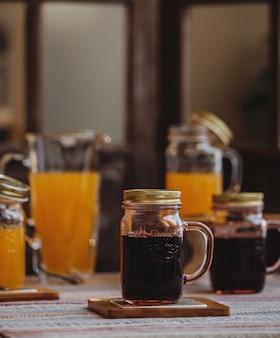 Seitenansicht des frischen kirschsaftes in einem glas auf einem kleinen holzständer