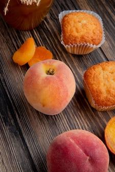 Seitenansicht des frischen reifen pfirsichs mit getrockneten aprikosen der muffins auf rustikalem holz