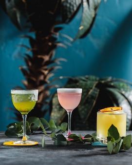 Seitenansicht des fruchtcocktails in einem glas, das mit getrockneten orangenscheiben auf grüner wand verziert wird