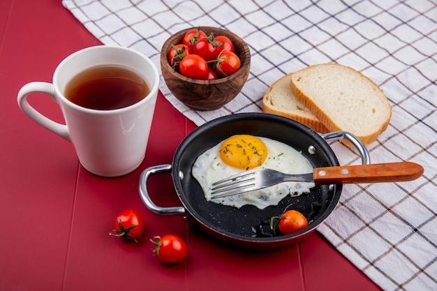 Seitenansicht des frühstückssatzes mit pfanne von spiegelei und tomate mit schüssel tomatenbrotscheiben auf kariertem stoff und tasse tee auf roter oberfläche
