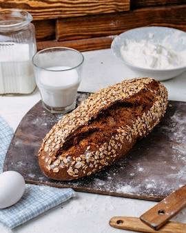 Seitenansicht des gebackenen brotes mit haferflocken und einem glas milch auf einem hölzernen schneidebrett