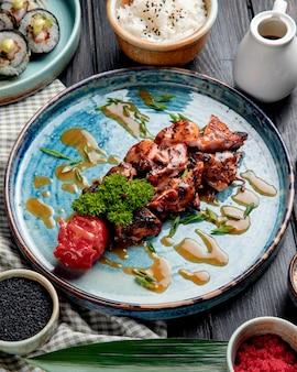 Seitenansicht des gebratenen huhns mit gegrillten frischen tomatenkräutern und soße auf einem teller auf holz