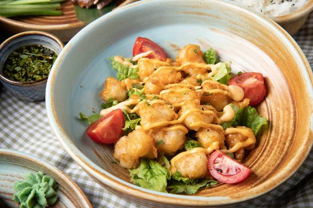 Seitenansicht des gebratenen huhns mit tomaten und soße auf salat auf einem teller auf rustikalem