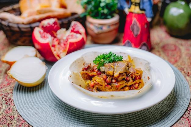 Seitenansicht des gedünsteten fleisches mit zwiebeln auf lavash auf einem weißen teller