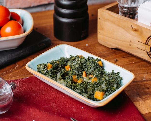 Seitenansicht des gedünsteten spinatsalats mit zwiebel und karotte auf einem holztisch
