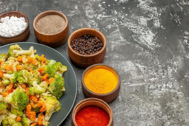 Seitenansicht des gemüsemehls mit brokkoli und karotten auf einem schwarzen teller und gewürzen auf grauem tisch