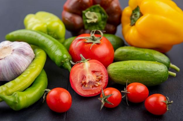 Seitenansicht des gemüses als geschnittener und ganzer tomatengurken-knoblauchpfeffer auf schwarz