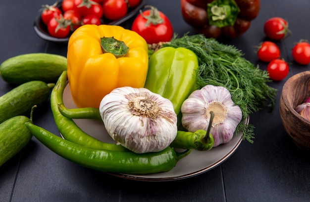 Seitenansicht des gemüses als knoblauchpfefferdill im teller mit gurken und tomaten auf schwarz