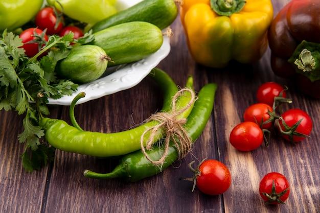 Seitenansicht des gemüses als pfefferkoriandergurke im teller mit tomaten auf holz