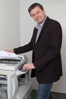 Seitenansicht des geschäftsmannes, der papier auf fotokopiergerät hält