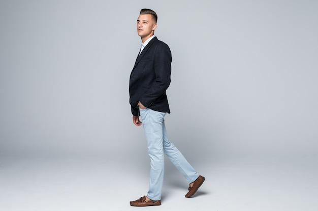 Seitenansicht des geschäftsmannes in der jacke und in den jeans bewegt sich durch studio, das auf weiß isoliert wird