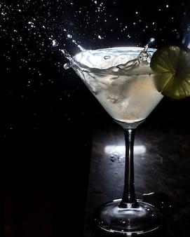 Seitenansicht des glases martini und des spritzens vom fallenden eis auf schwarz