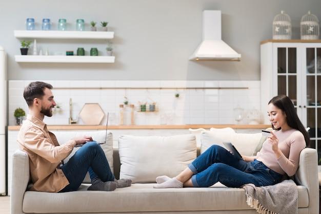 Seitenansicht des glücklichen paares auf dem sofa, das online einkauft