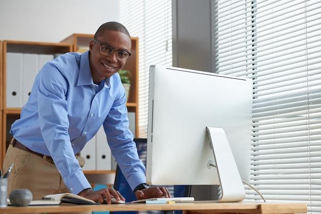 Seitenansicht des glücklichen startupper, der den computermund verwendet und kamera betrachtet